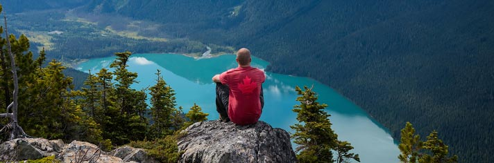 Man in the Canadian Rockies overlooking a lake wearing a red maple leaf shirt.